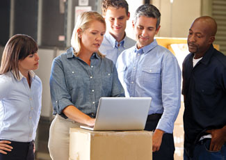 a small group of warehouse staff gather around a laptop