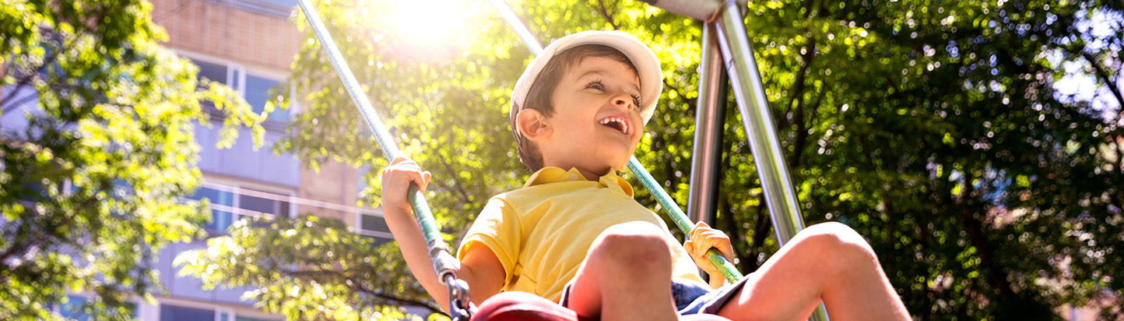 delighted young boy on swing (image from https://www.istockphoto.com/ca/photo/happy-kids-playing-outdoor-at-the-park-gm967909366-263977324)